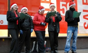 Carol singers wearing Santa hats on a pavement in Glasgow